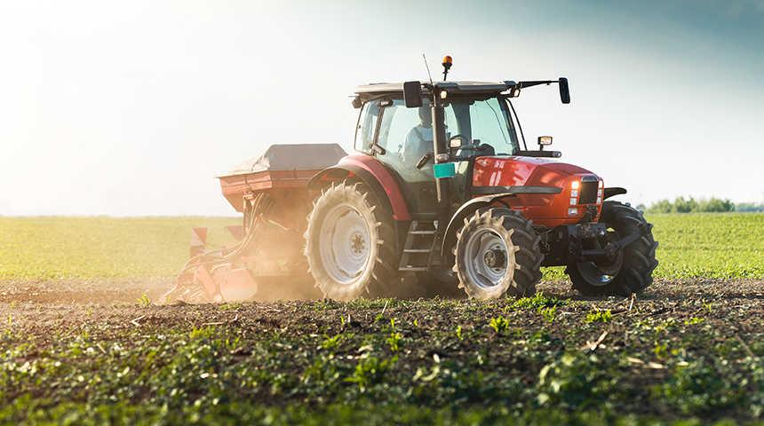 Tracteur rouge dans un champ vert